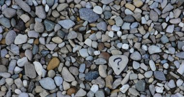 question / Muscular Dystrophy News / Photo of a bunch of small rocks. A gray one in the center has a question mark on it.
